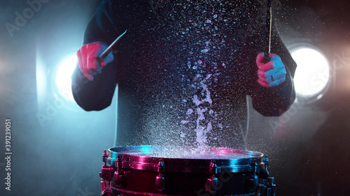 Canvas Print Freeze motion of drummer hitting drum with water splashes