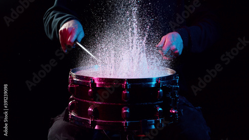 Fotografia Freeze motion of drummer hitting drum with water splashes