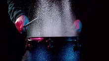 Freeze Motion Of Drummer Hitting Drum With Water Splashes