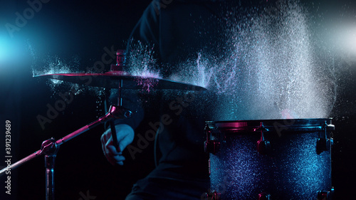 Fotografia Freeze motion of drummer hitting drums with water splashes