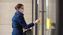 Side View Of Businesswoman Putting On Safety Mask And Entering Office Building