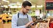 Leinwandbild Motiv Close up portrait of happy Caucasian male worker in glasses standing in supermarket and typing on tablet. Young joyful man food store assistant at work tapping on device indoors. Retail concept