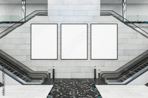 Modern shopping center with escalator and three blank posters