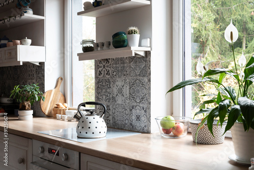 Fotografie, Obraz Interior of kitchen in white color with modern tiles in grey decor and window with plant