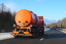 Modern Orange Semi Truck Fuel Tanker With Move On Highway At Sunny Winter Day In Perspective On Blue Sky And Bare Treees On Roadside Background, Rear Side View Dangerous Cargo