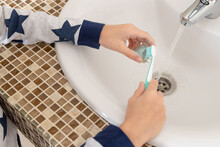 Children's Hands Cleaning Dental Plate With Toothbrush Over Bathroom Sink. Dental Health, Retainer Teeth Care Concept. Close-up.