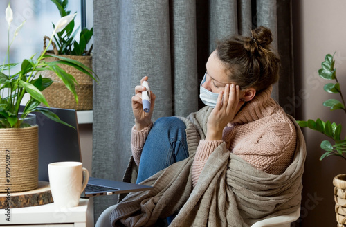 Slika na platnu Sick European attractive young woman caught a cold and looks at the thermometer Upset young blonde in a sweater and blanket feels bad, wears a medical mask