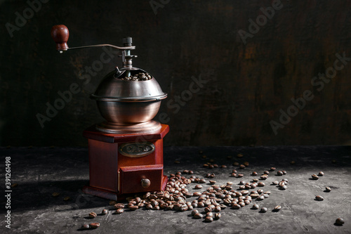 Nostalgic wooden coffee grinder and roasted coffee beans in side light against a Fotobehang