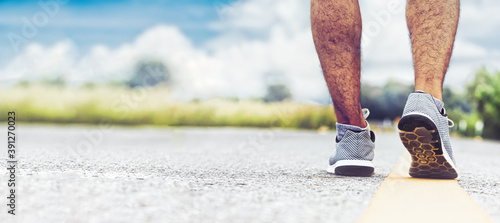 Fotografia young man jogging on the road in an outdoor park with copy space, running for ex