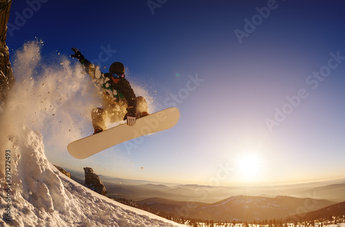 Fotografia Snowboarder jumping against the sunset sky
