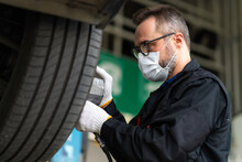 Professional Car Mechanic Changing Car Wheel At Car Maintenance And Auto Service Garage. Caucasian Man Worker People. Surgical Face Mask Protec Coronavirus Covid 19.