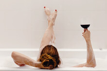 Woman Drinking Red Wine While Taking Bath With Foam