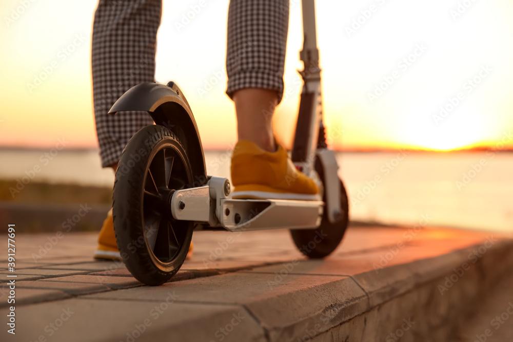 Fototapeta Woman riding electric kick scooter outdoors at sunset, closeup