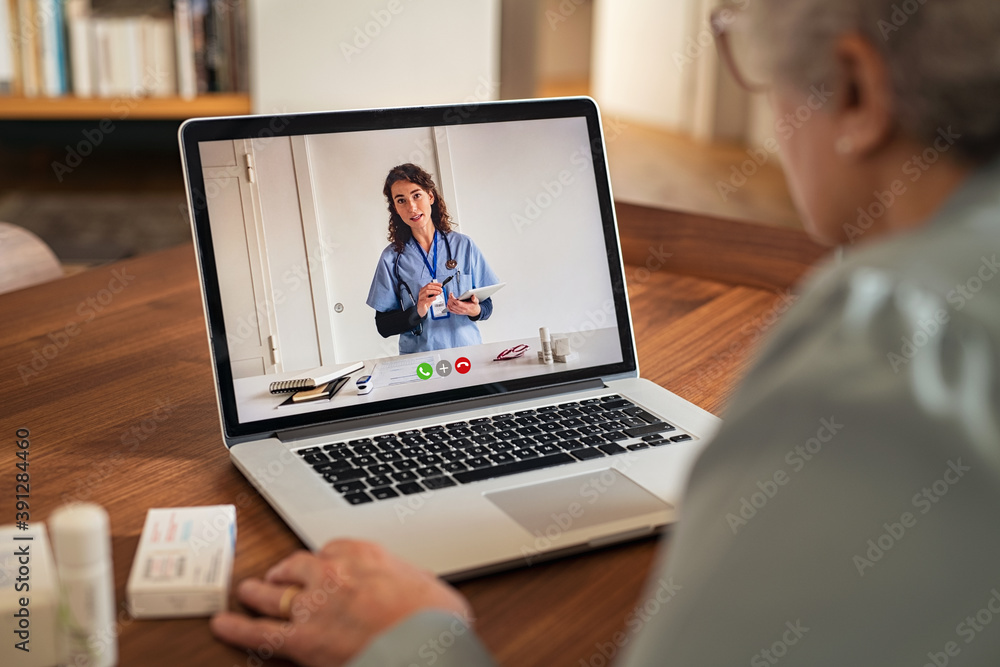 Fototapeta Senior woman in video tele medicine call with doctor