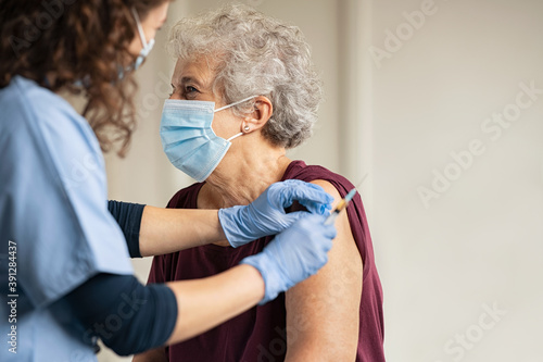Obraz na plátne Doctor giving Covid vaccine to senior woman