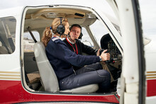 Pilot In Training And Flight Instructor In The Cockpit Of An Airplane. Female Pilot With Headphones Preparing To Fly. He Is Sitting Next To The Female Instructor Attending To Her Explanations.