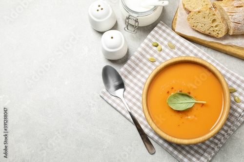 Tasty creamy pumpkin soup with basil in bowl on grey table, flat lay. Space for text