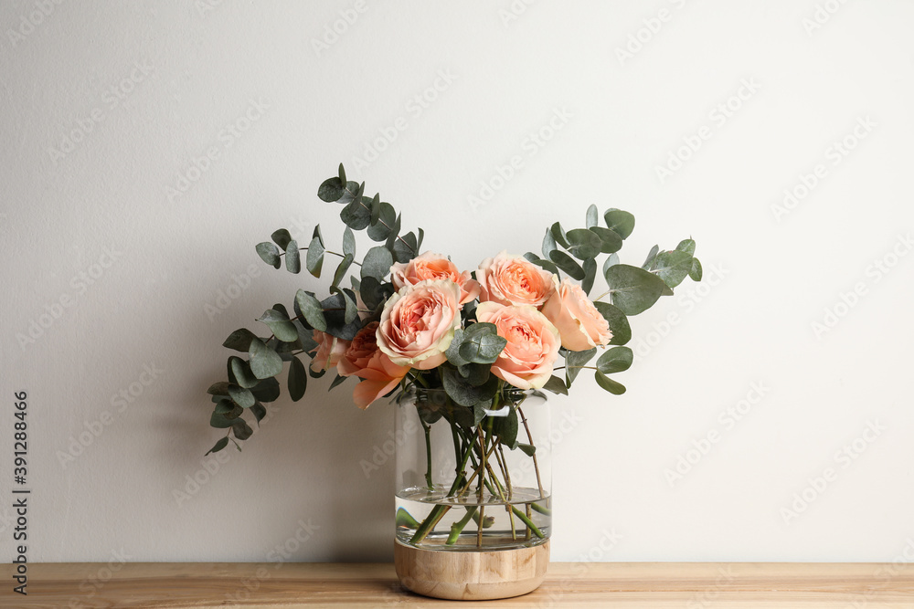 Fototapeta Bouquet with beautiful flowers in glass vase on wooden table against white background
