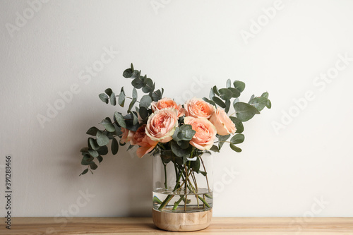 Bouquet with beautiful flowers in glass vase on wooden table against white background