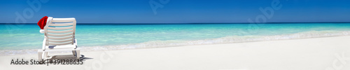Santa Claus Hat on sunbed near tropical beach with turquoise caribbean sea water and white sand