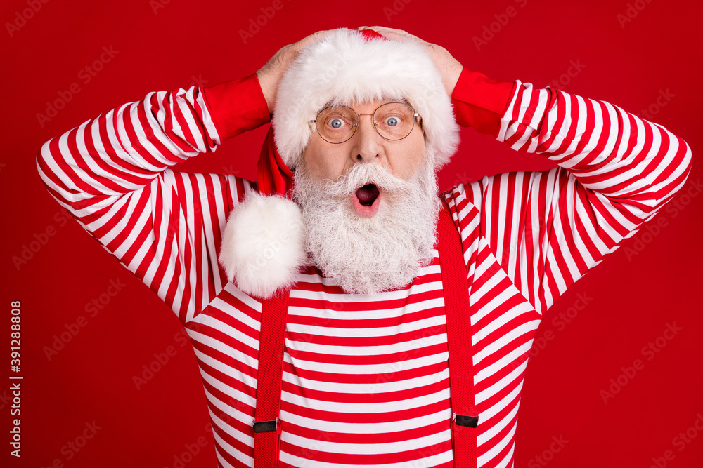 Fototapeta Photo of pensioner old man surprised open mouth hands head good news deer online shop sale wear santa costume suspenders spectacles striped shirt headwear isolated red color background