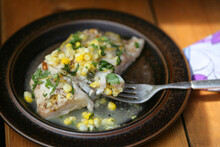 Gourmet Cooked Fish With Corn And Herbs On Top On Plate