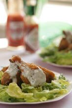 Fried Chicken Drumsticks With Sauce And Lettuce On Plate