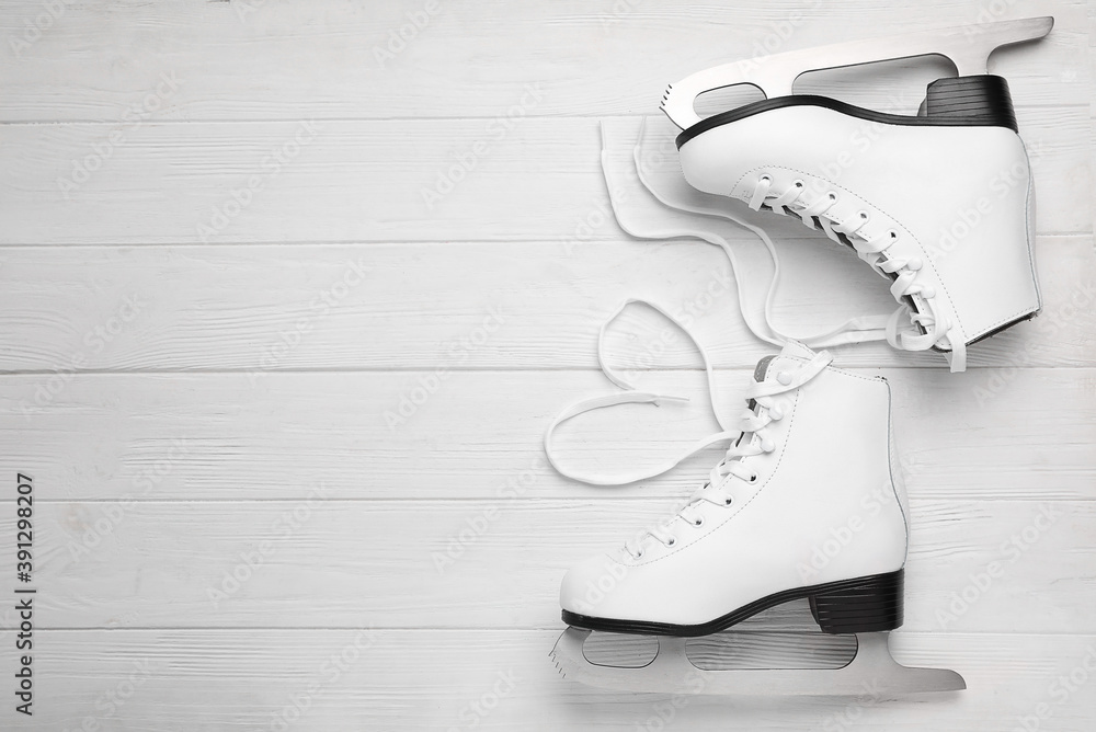 Fototapeta Pair of ice skates on white wooden background, top view. Space for text