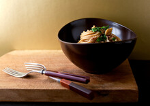 Spaghetti With Walnuts And Anchovies In Bowl On Cutting Board