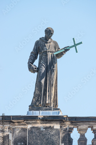 Banner with old roof church statute of high ranked priest with a cross and human skull in historical downtown of Dresden, Germany, details, closeup, with copy space for text Canvas Print