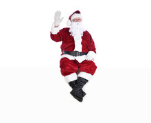 Senior Man In Traditional Santa Claus Suit Sitting On A White Wall Waving.  Isolated On White With Copy Space.