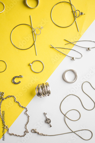 Slika na platnu Silver jewelry on minimal yellow background. minimal art