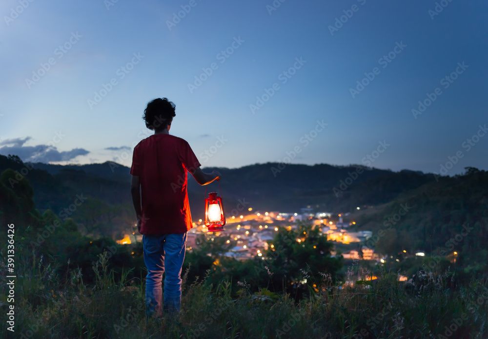 Fototapeta Man holding a lit kerosene lamp on the top of the mountain and watching the city lights in the valley. Electric power.