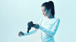 Athletic young female massaging hand by handheld massage gun in neon light, post-workout recovery routines