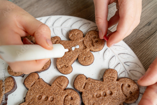 Horizontal top view of little unrecognizable family decorating with sugar frosting Christmas cookies Canvas