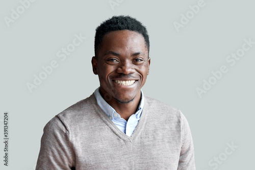 Obraz Smiling cheerful young adult african american ethnicity man looking at camera standing at home office background. Happy confident black guy posing for headshot face front close up portrait. - fototapety do salonu