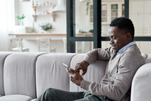 Relaxed Smiling African American Man Holding Digital Tablet Computer Using Apps Sitting On Couch At Home. Black Guy Remote Learning, Social Distance Working, Ordering Buying Online Or Reading E Book.