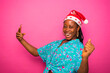 Leinwandbild Motiv overexcited black african female millenial celebrating with her smart phone after receiving good news. wearing xmas hat standing behind a pink studio wall. christmas concept