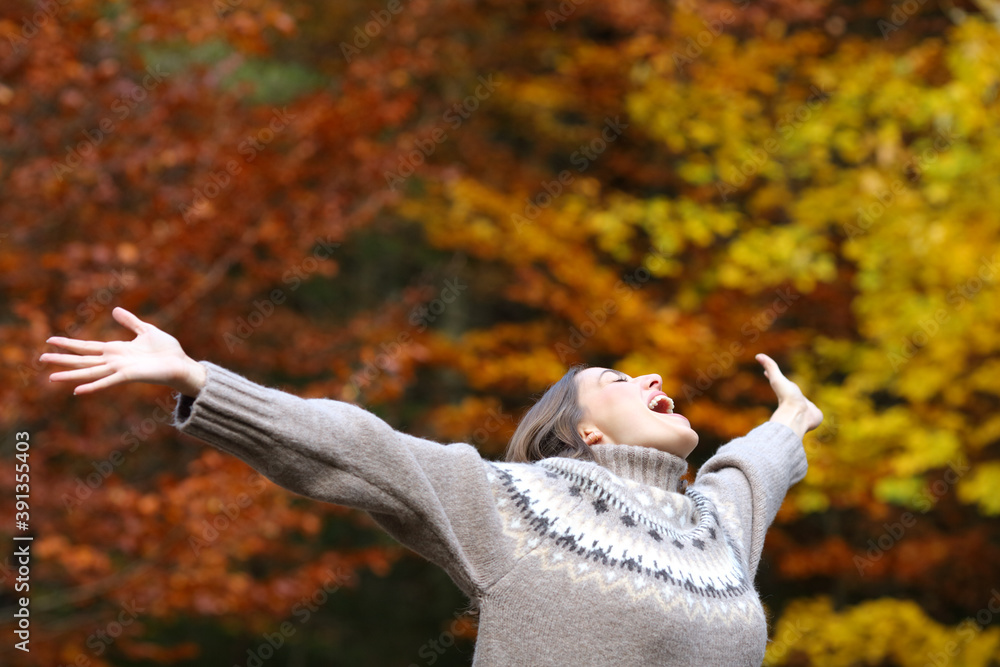 Fototapeta Excited woman celebrating autumn stretching arms