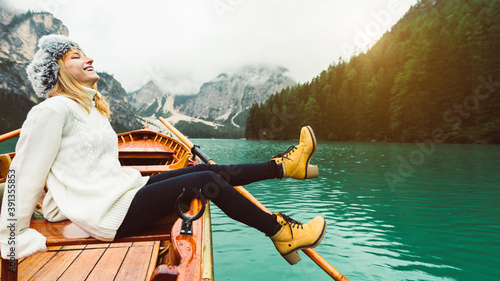 Obraz Tourist woman in traditional wooden rowing boat on italian alpine Braies Lake - Girl enjoying stunning view of Lago di Braies in Dolomites, South Tyrol, Italy, Europe. - fototapety do salonu