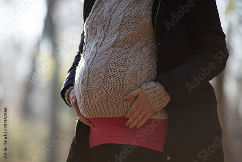 Fototapeta Pregnant woman touching her swollen belly in winter clothes