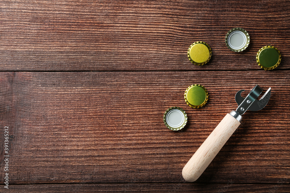 Fototapeta Bottle caps with opener on brown wooden table