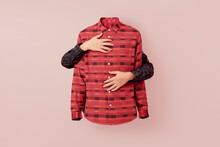 Two Caucasian Hands Hands Are Wrapped Around A Pink Patterned Shirt