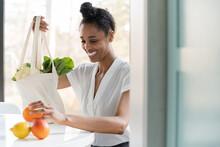 Woman Unpacking Reusable Tote Bag Full Of Groceries