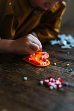Toddler Making A Iron Beads Heart