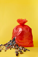 A Large Red Bin Bag Splits Open Spilling A Glut Of Trainers And Shoes