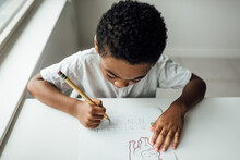 Boy Coloring And Writing At The Kitchen Table