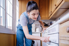 Woman Using The Controllers Of The Oven.