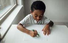 Boy Coloring And Writing At Th...
