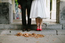 Bride With Bright Red Shoes With Bow Standing Next To Groom Dressed In Black With Brow Shoes